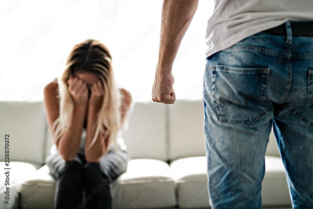Fototapeta Man beating up his wife illustrating domestic violence