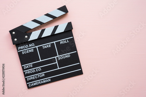 Valokuvatapetti Cinema clapperboard on pink wooden background - Movie entertainment concept
