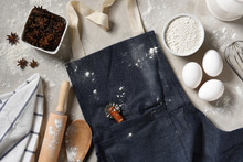A Denim Apron With Eggs, Flour And Equipment For Making Holiday Cookies And Desserts