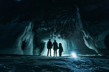 Surreal Landscape With People Exploring Mysterious Ice Grotto Cave. Outdoor Adventure. Family Exploring Huge Icy Cave, Dark Majestic Landscape. Magical Silhouettes On Background Of Illuminated Ice.