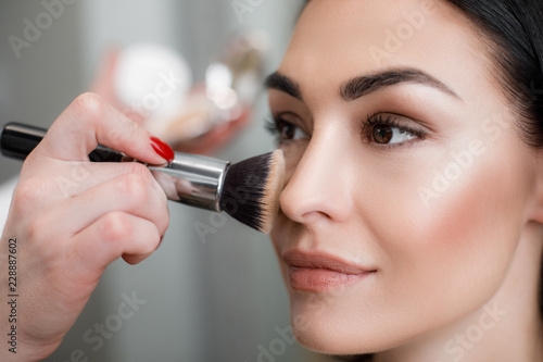 Obraz Close up of makeup artist applying light layer of matting powder while using professional brush for lady - fototapety do salonu
