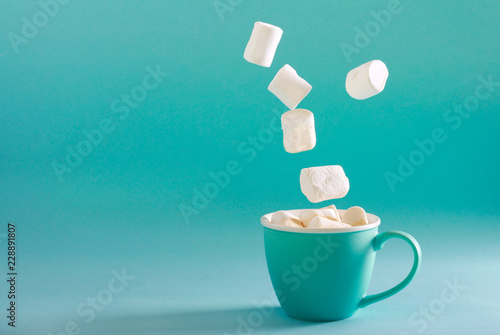 Marshmallow falling into cup over bright turquoise