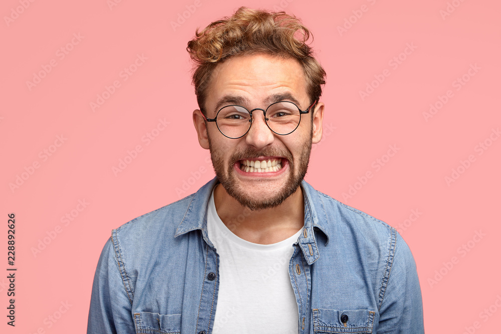 Fototapety, obrazy: Photo of pleased curly Caucasian man smiles joyfully at camera, clenches teeth, dressed in fashionable blue shirt, being in good mood after date with girlfriend, poses against pink background