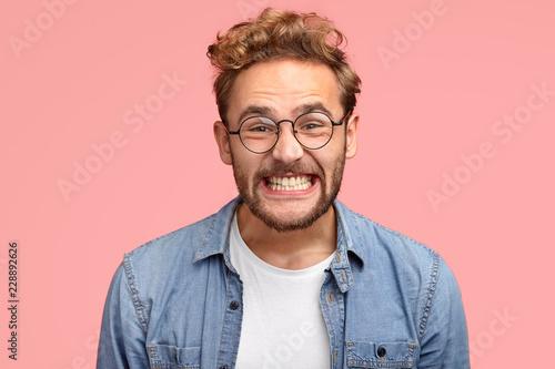 Fotografia  Photo of pleased curly Caucasian man smiles joyfully at camera, clenches teeth,