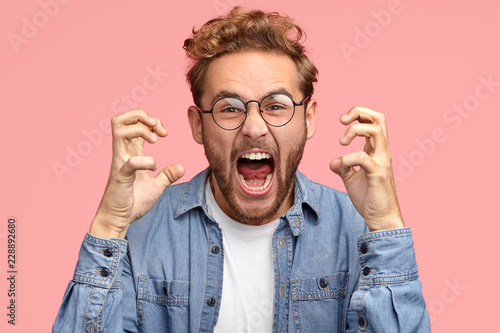 Fototapeta  Peevish annoyed man gestures angrily, expresses negative emotions, keeps mouth widely opened, screams fron irritation, dressed in casual shirt, poses against pink studio wall