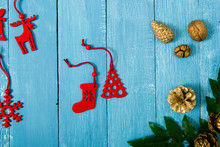 Christmas Decoration Background With Holly Leaves And Red Felt Ornaments On Old Blue Wooden Table
