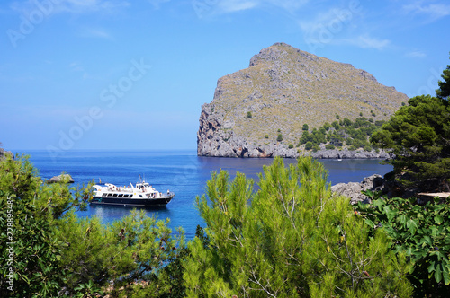 Passenger ship sailing past a cliff off the coast of the island of Majorca, Spain