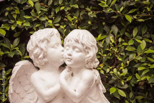 Fotografia Vintage style cute cupid kiss angel statue in green garden, valentine romantic d