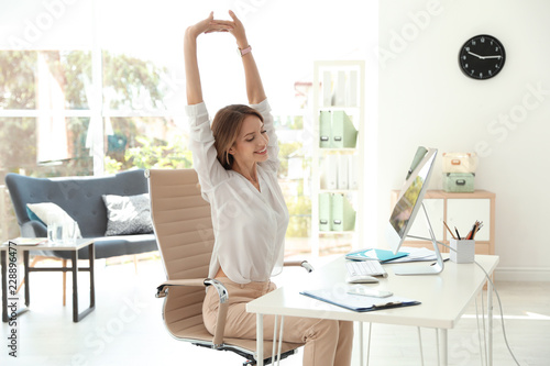 Young beautiful businesswoman stretching in office Fototapeta
