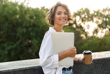 Beautiful Woman Walking Outdoors Holding Laptop Computer Holding Coffee.