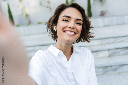 Fotomural Cheerful young woman in earphones standing at the street