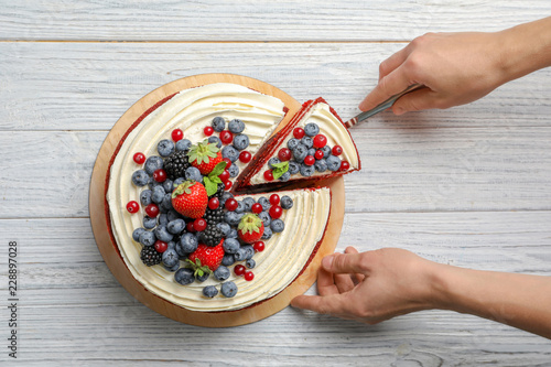 Woman taking piece of delicious homemade red velvet cake from table, top view