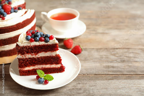 Plate with piece of delicious homemade red velvet cake and space for text on wooden table