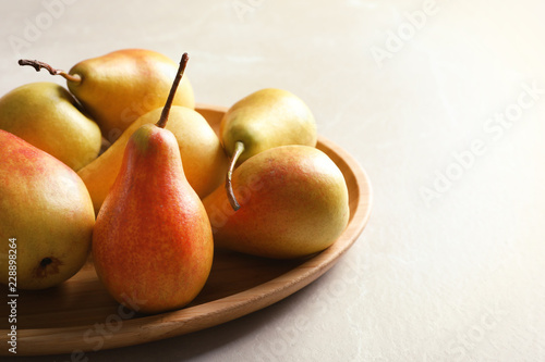 Plate with ripe pears on light background, closeup. Space for text
