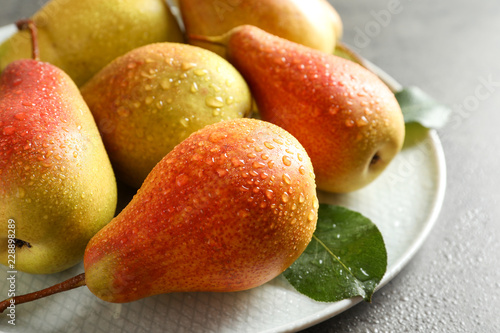 Plate with ripe pears on grey background, closeup