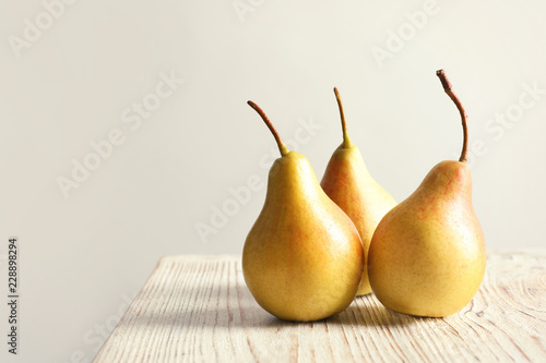 Ripe pears on wooden table against light background. Space for text