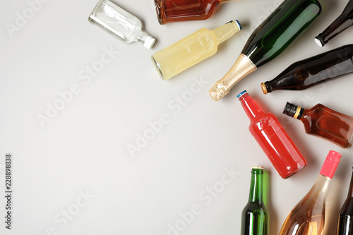 Bottles with different alcoholic drinks on light background, top view. Space for text