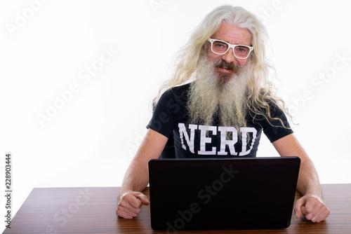 Fotomural Studio shot of happy senior bearded nerd man smiling while weari