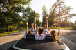 Company of young people riding in a cabriolet on the road and holding their hands up on a warm sunny day.