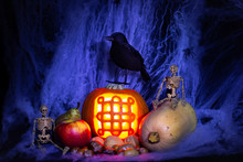 Samhain/celtic New Year/halloween Still Life With Samhain Symbol Carved Into A Lit Pumpkin Among Autumn/fall Vegetables, Fruit, Nuts, Two Toy Skeletons & Toy Black Bird With A Spiderweb Background