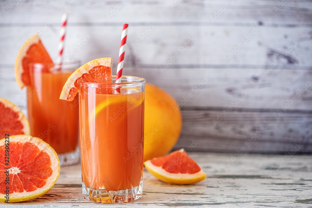 Fototapeta Fresh grapefruits and two glasses of grapefruit juice on light wooden table. With copy space