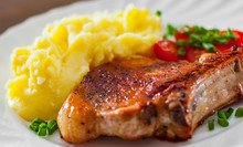 Grilled Pork Loin Meat With Mashed Potatoes And Salad In White Plate