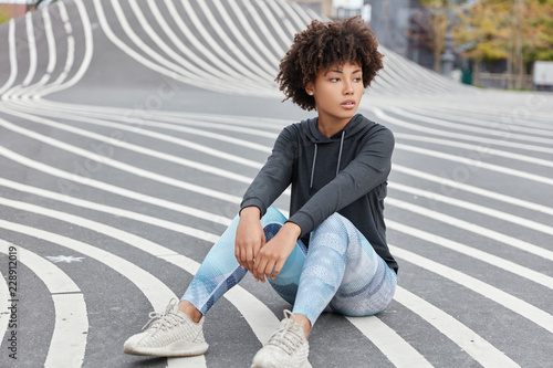 Fotografía  Outdoor shot of pensive dark skinned teenager dressed in casual sportsclothes, sneakers, sits on asphalt, recreats after having sport competitions, has fit body