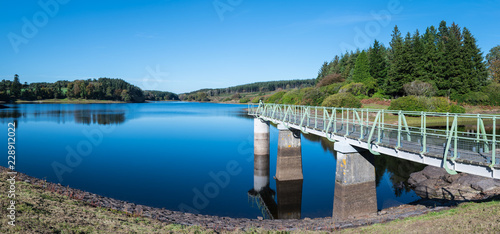 Canvas Print Panorama of Kennick Reservoir in Dartmoor National Park, England, UK, on a bright clear day with the intake tower gantry stretching out, reflections in the water and trees and boats in the background