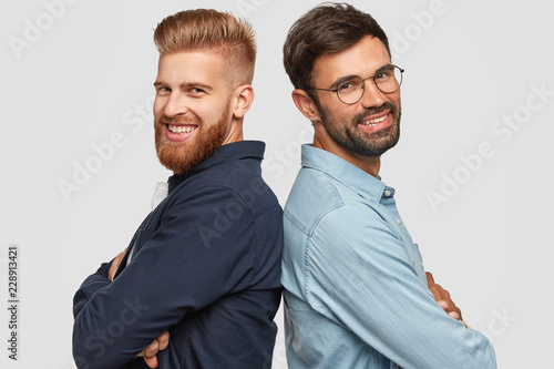Fototapeta Best friend stand back to back, have friendly relationships, keep hands folded, smile gladfully, work as team, isolated over white background. Happy foxy bearded man and his partner pose indoor obraz