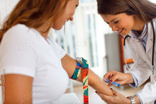 Fototapeta Nurse takes blood from the patient's hand