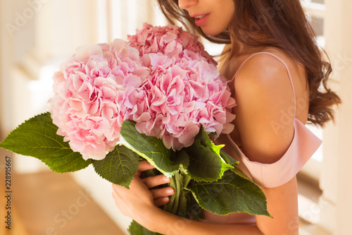 Stickers pour portes Hortensia Beautiful woman holding a pink hydrangeas in her arms.