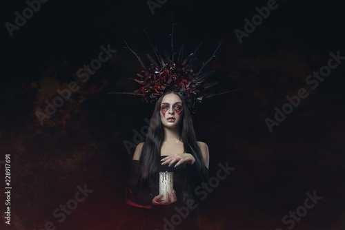 Ingelijste posters Halloween Terrible Halloween Vampire Woman portrait. Beauty Vampire Witch lady with blood on mouth posing in deep forest. Fashion Art design. holds a candle in his hands and reads curses