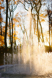Splashing fountain in autumn park, sunset on background, close up. Beautiful sunset through water fountain, vertical. Autumn time in the city park