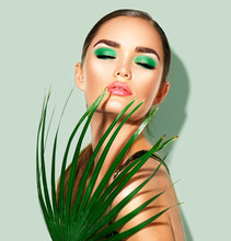 Beauty Woman With Natural Green Palm Leaf. Portrait Of Model Girl With Perfect Makeup, Green Eyeshadows