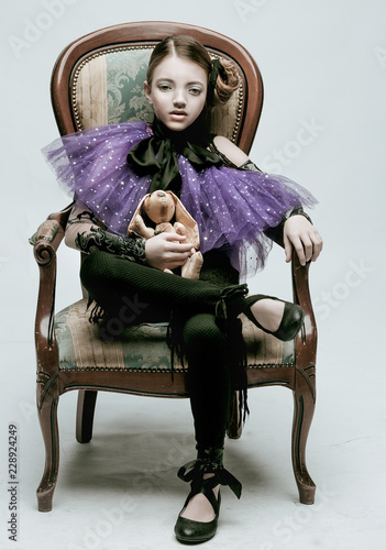 Beautiful girl child model in fashionable clothes holding a rabbit toy Fototapet