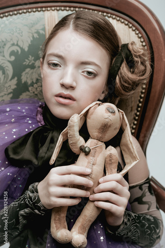 Tablou Canvas Beautiful girl child model in fashionable clothes holding a rabbit toy