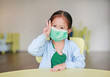 Cute little Asian child girl wearing a protective mask with showing two fingers for fight sitting on kid chair in children room.