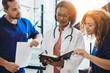 Leinwanddruck Bild - Diverse group of doctors talking together in a hospital corridor