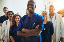 Smiling African Doctor Standing In A Hospital With His Staff