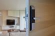 Wood door half open with digital knob door or handle in front of blur interior background