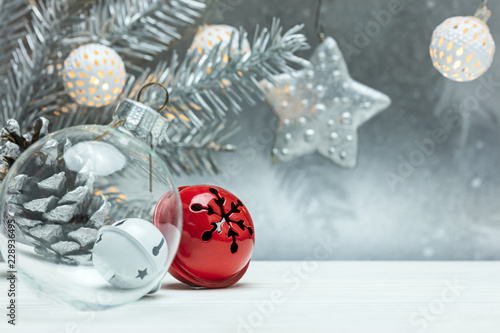 christmas tree decorations on blurred silver background with fir tree branch and retro garlands