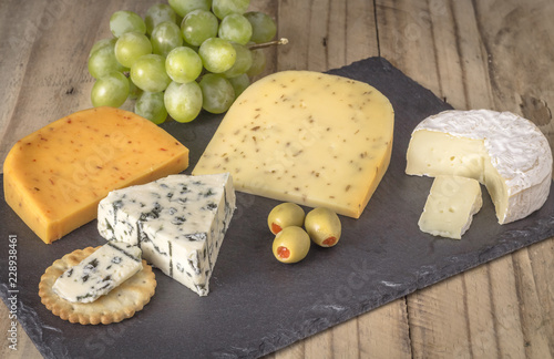 Cheese board with four cheeses, gouda with pimento, gouda with cumin seeds, camembert and roquefort blue cheese close up on rustic wooden background