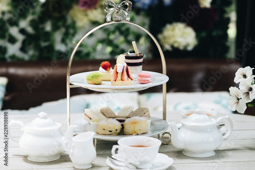 Fototapeta Traditional English afternoon tea: scones with clotted cream and jam, strawberries, with various sandwiches on the background obraz