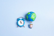 Light Bulb With Plasticine Earth Planet Model And Alarm Clock On Yellow Background. Global Ecology, International Day Of Energy Saving Or Earth Hour Concept.