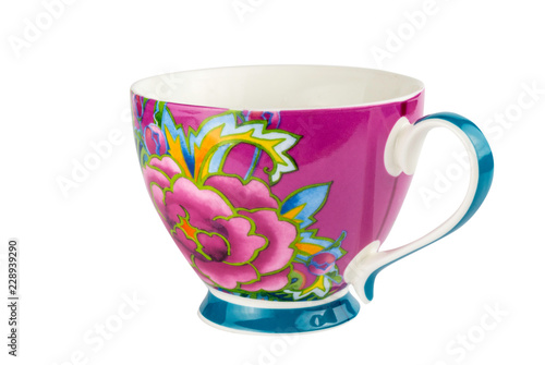 Mug cup for tea or coffee brightly decorated in pink blue and yellow colours - hand painted oriental style cup isolated on white background