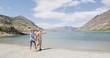 New Zealand travel happy tourist couple walking at beach shore of lake Hawea nature landscape. Near Wanaka, Otago Region.