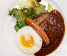 Hamburger Steak With Demi Glace Sauce, Egg, Sausage And Vegetable On The White Plate