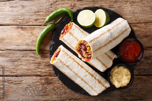 Mexican popular grilled burrito snack with beef and vegetables and with sauces close-up. horizontal top view