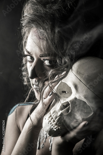 Fototapety, obrazy: Portrait of the woman with halloween makeup close up. Talking with skull, which is in front of her. Isolated image on black background with the smoke and beautiful studio light.