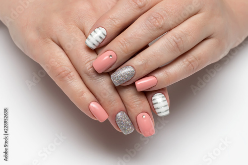 Montage in der Fensternische Maniküre Pink, beige white manicure with silver stripes, crystals, silver glitters on short square nails on a white background close-up